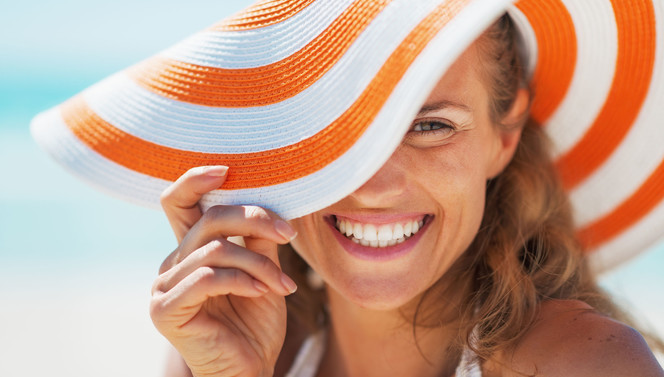 Woman with orange beach hat in the sun