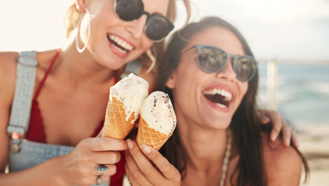 Women eat ice cream on the beach in the summer